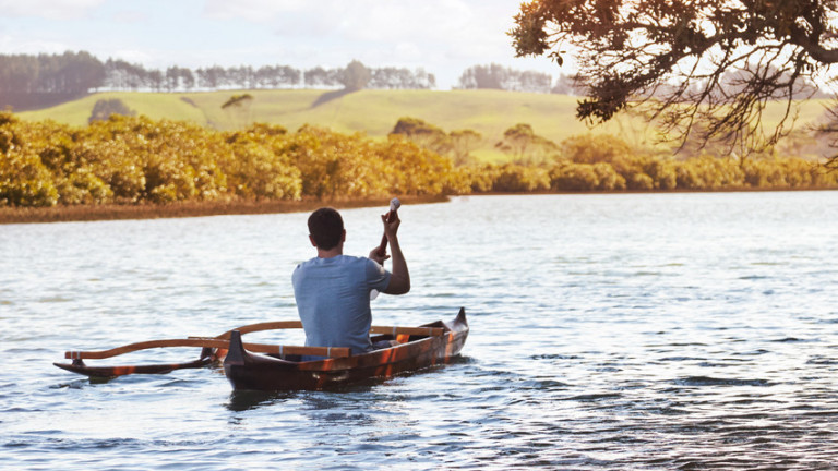 Image of a young man paddling an outrigger waka on a river